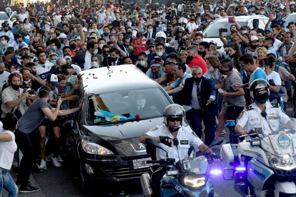 Der Leichenwagen mit den sterblichen Überresten von Diego Maradona verlässt das Regierungsgebäude begleitet von Fans