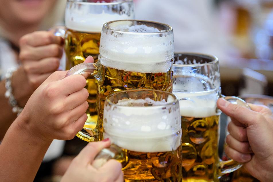 Besucher stoßen auf dem Oktoberfest mit Bier an.
