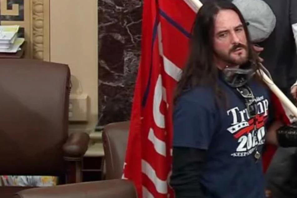 Paul Allard Hodgkins was photographed carrying a Trump flag through the Senate chamber.