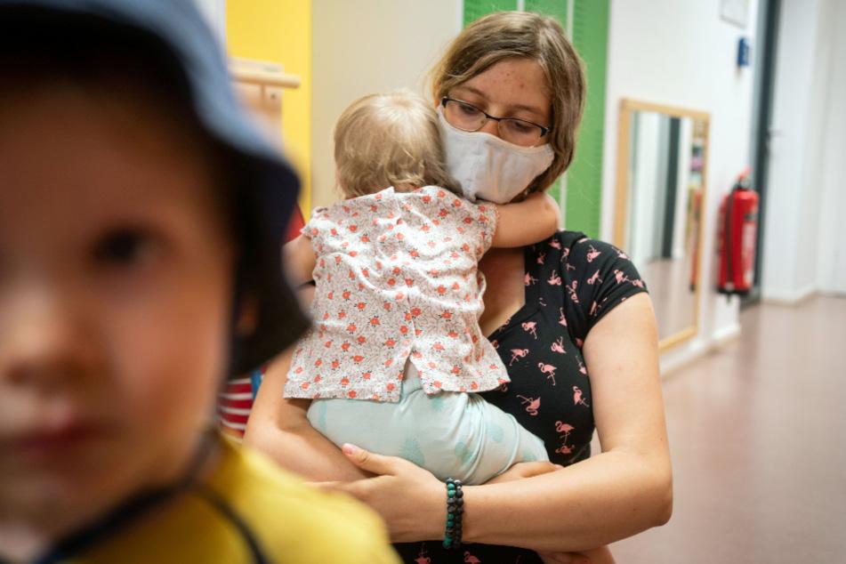 Hessen, Frankfurt/Main: Eine Erzieherin mit Mundschutz hält einen ihrer Schützlinge in einer Kindertagesstätte im Stadtteil Bornheim im Arm.