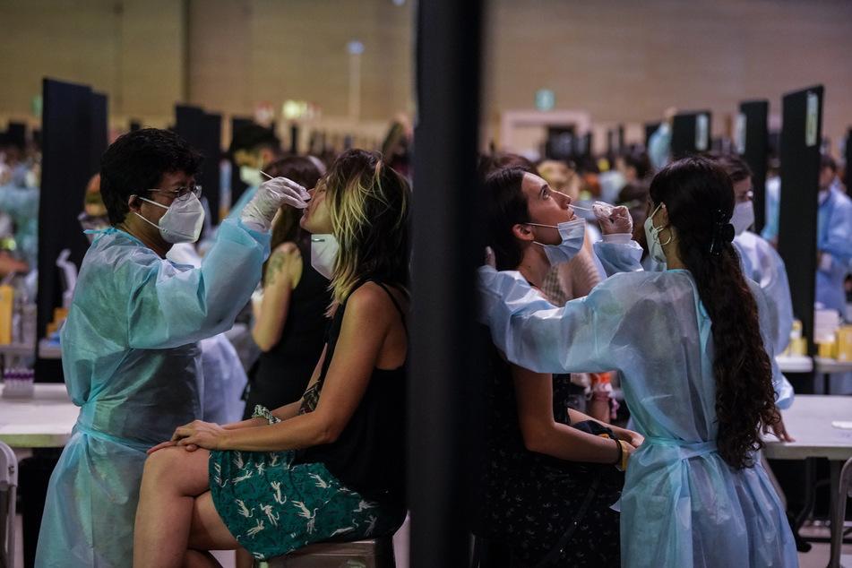 Mitarbeiter des Gesundheitswesens sammeln Abstrichproben für einen Corona-Schnelltest vor dem Cruilla-Musikfestival.