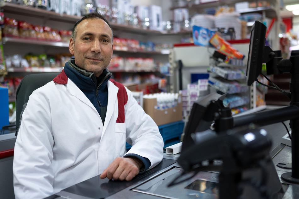 Verkäufer Selami Toktas sitzt in seinem Lebensmittelgeschäft an der Kasse.