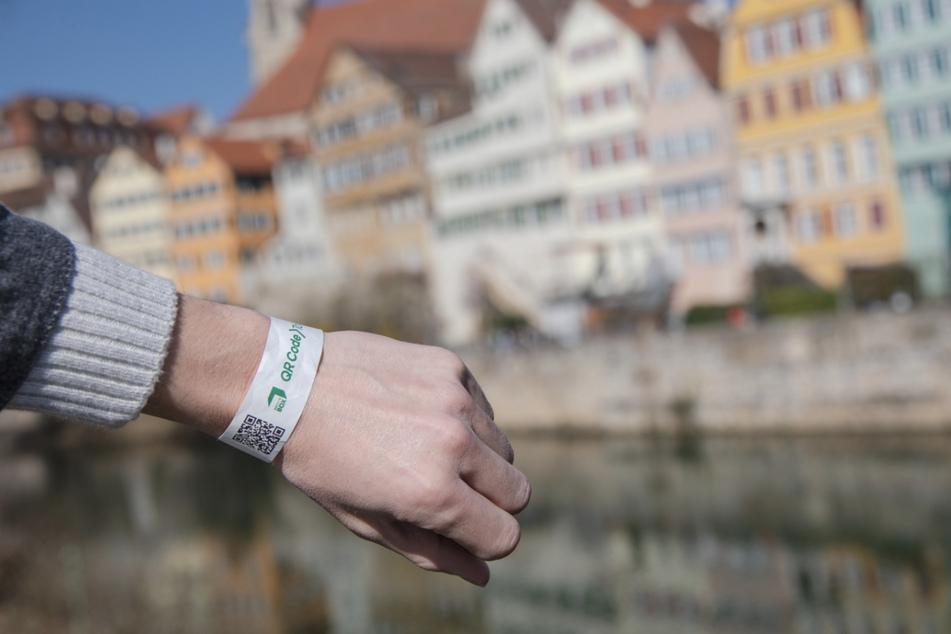 Ein Mann trägt in Tübingen ein Tagesticket-Armband. Die Stadt stellt das Tagesticket auf ein digitales System um. Wer sich an einer der neun Stationen im Stadtgebiet auf Corona testen lässt, bekommt künftig ein Armband mit einem QR-Code, welches nicht weitergegeben werden kann.