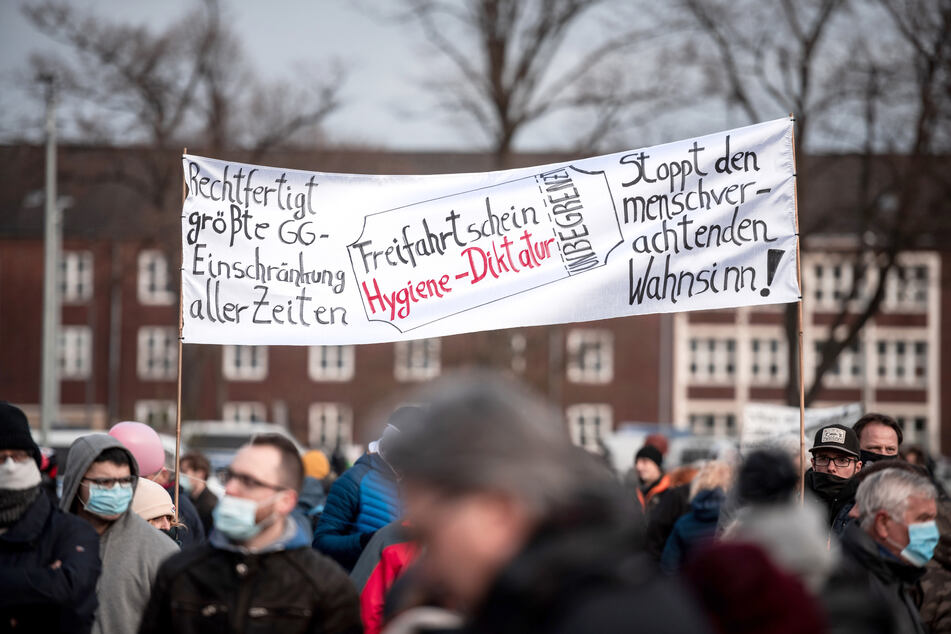 """Teilnehmer einer Demonstration der Initiative """"Querdenken 234 Bochum"""" halten einen Banner."""