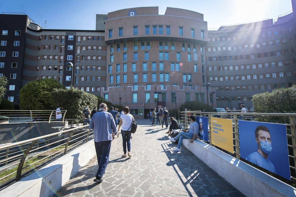 Personal, Besucher und Patienten gehen vor dem Krankenhaus San Raffaele, wo der ehemalige italienische Ministerpräsident Berlusconi ins Krankenhaus stationär aufgenommen wurde.