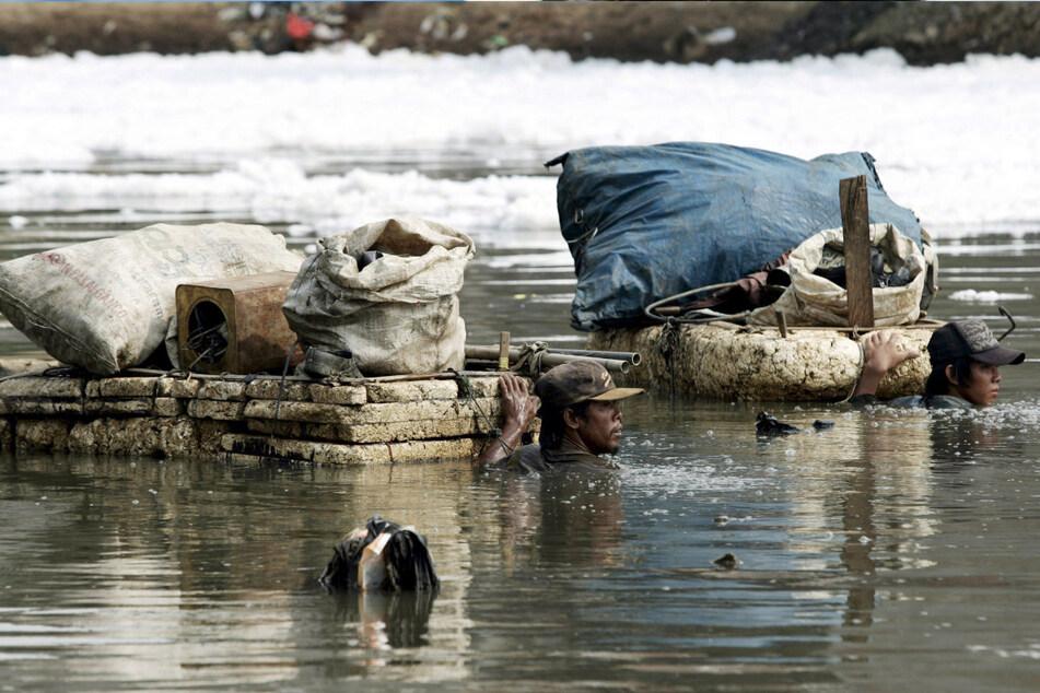 Menschen sammeln Dosen und Kunststoffe aus einem verschmutzten Fluss in Jakarta. Auch der Müll in Gewässern lässt viele Arten sterben.