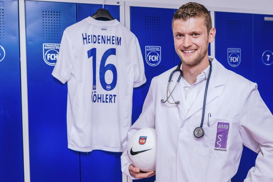 Tim Göhlert, damaliger Fußballspieler beim Zweitligisten 1. FC Heidenheim in seiner letzten Saison, steht in einem Arztkittel in der Kabine des Fußballclubs in Heidenheim.