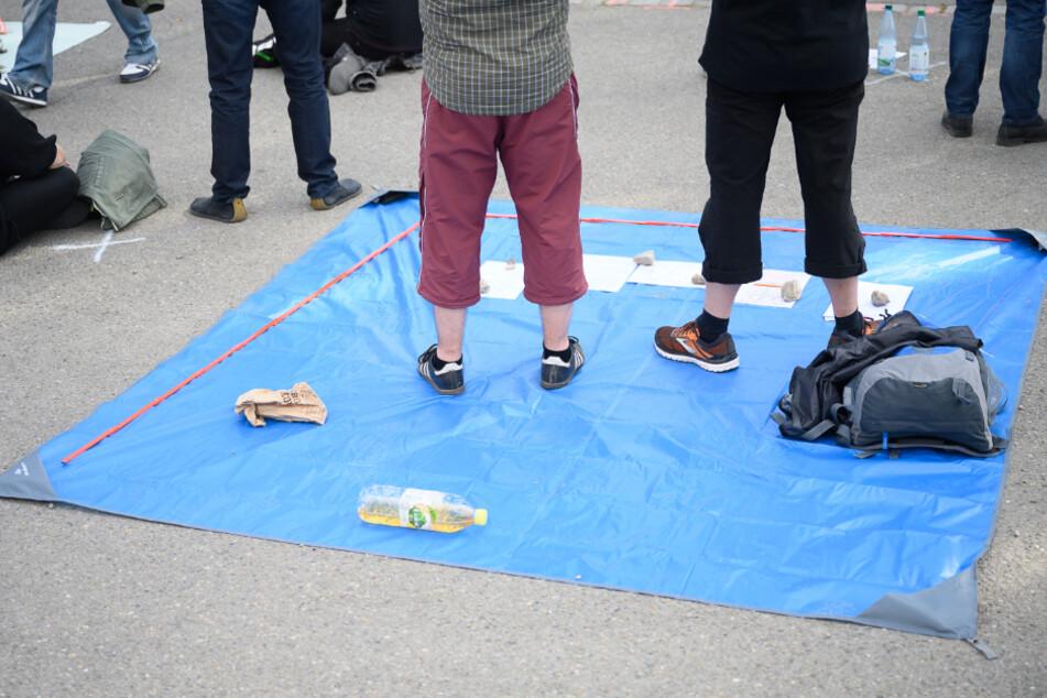 Zwei Männer stehen auf einer Plane, mit der sie den Abstand zu den anderen Demonstranten markieren.
