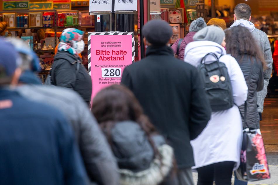 """Ein Schild mit der Aufschrift """"Bitte haltet Abstand - Momentan können wir nur 280 Kunden in den Store lassen"""" steht vor den Eingang eines Warenhauses in der Fußgängerstrasse in München."""