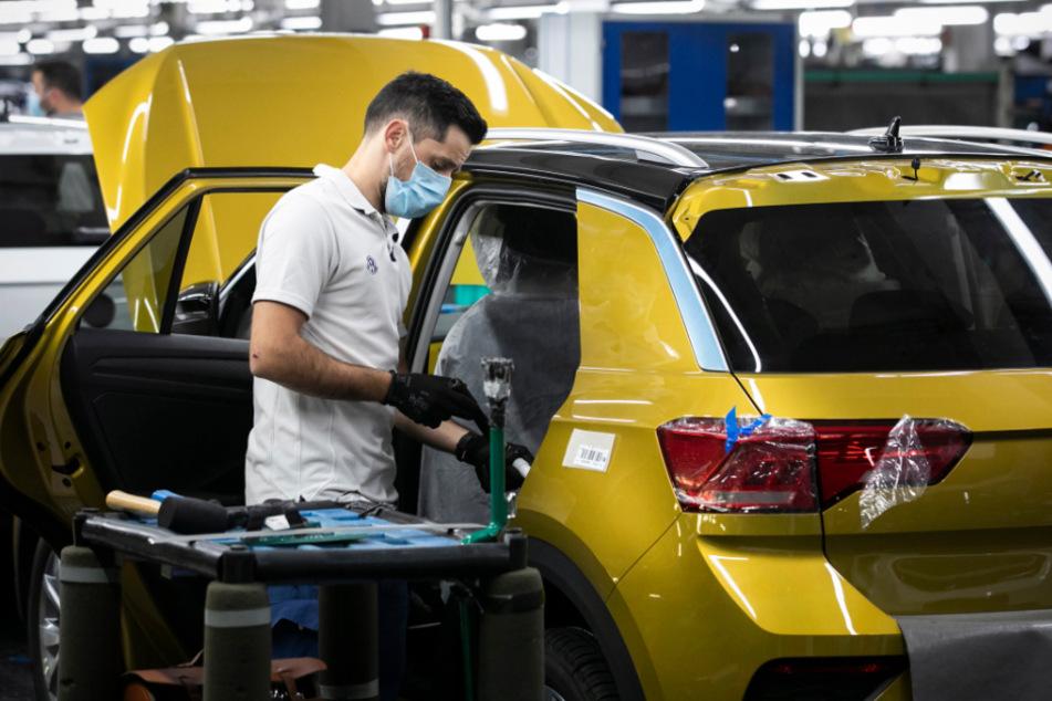 Ein Angestellter mit Mundschutz arbeitet an der Montagelinie an einem Volkswagen T-Roc im portugiesischen Autowerk von Volkswagen Autoeuropa. Das Werk nahm nach anderthalb Monaten, in denen durch die Corona-Pandemie nicht produziert wurde, die Produktion wieder auf.