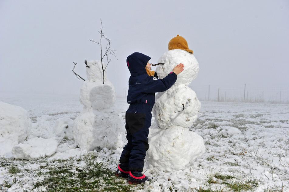 Die richtige Kopfbedeckung ist der kleinen Schneekünstlerin Martha-Magdalena (4) bei ihrem Schneemann wichtig - ebenso, dass er nicht frieren muss.