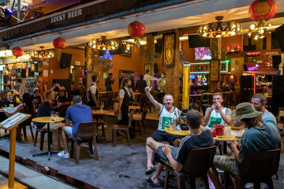 Thailand, Bangkok: Menschen trinken in einer Bar in der Khao San Road, im Hintergrund tragen die Angestellten Mundschutz.