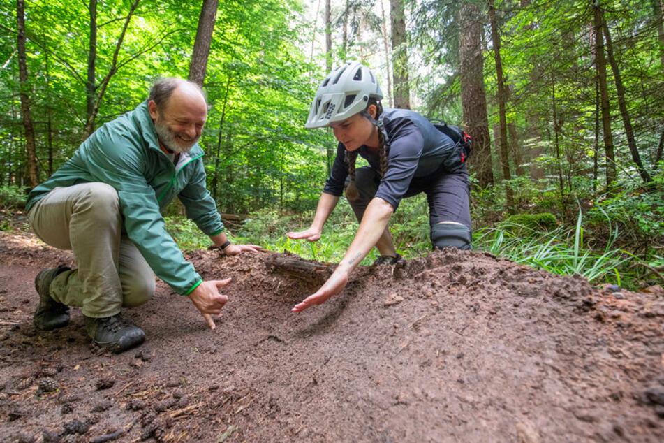 Hans-Joachim Ulrich, Förster bei den Bayerischen Staatsforsten, und Nora Beyer von der Nürnberger DIMB (Deutsche Initiative Mountainbike), unterhalten sich an einer selbst ausgearbeiteten Steilkurve im Nürnberger Reichswald.