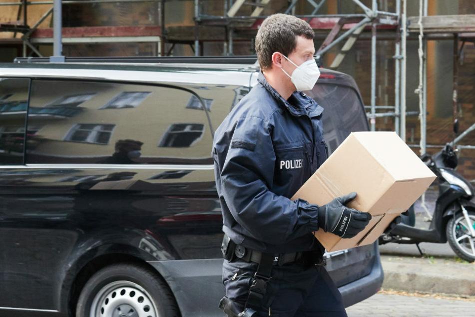 Ein Polizist trägt einen Karton, der bei einer Razzia sichergestellt wurde. Die Polizei Berlin ist am Dienstag gegen fünf mutmaßliche Menschenhändler vorgegangen. (Symbolfoto)