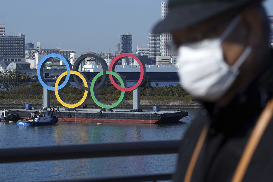Ein Mann, der eine schützende Gesichtsmaske trägt, um die Ausbreitung des Coronavirus einzudämmen, geht nahe der Olympischen Ringe in der Bucht von Tokio.