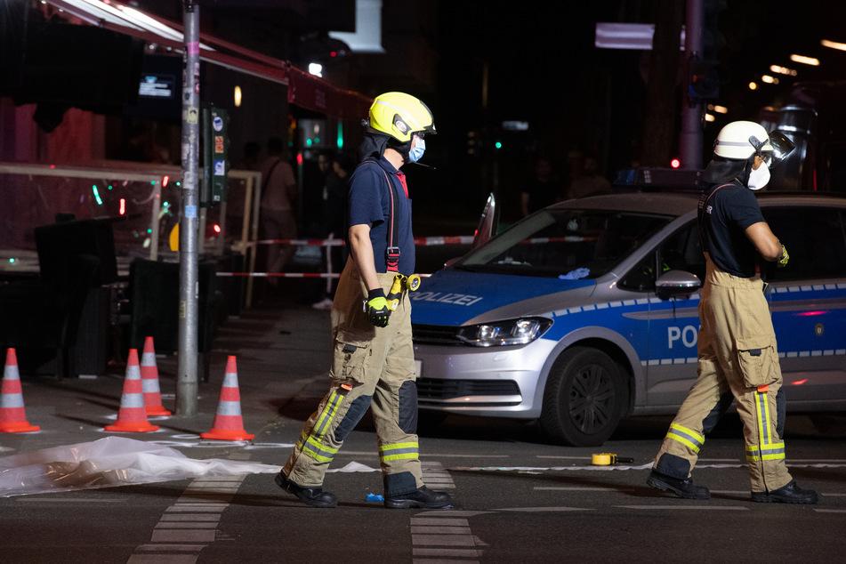 Feuerwehrleute gehen auf der Müllerstraße an Leitkegeln vorbei. In Berlin-Wedding sind am späten Sonntagabend vermutlich mehrere Schüsse gefallen.