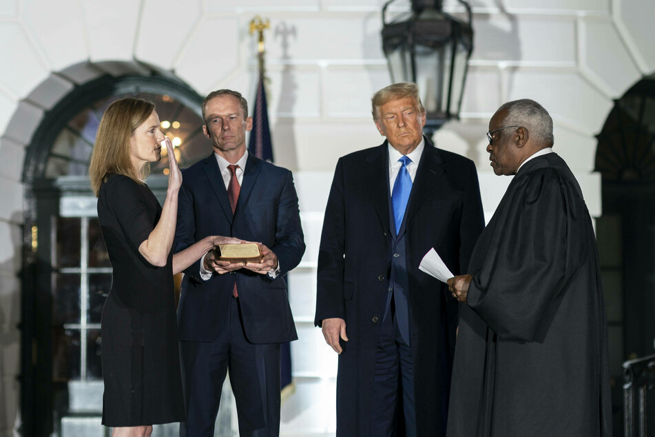 Justice Amy Coney Barrett, seen here being sworn in by Justice Clarence Thomas, did not take part in the deliberations.