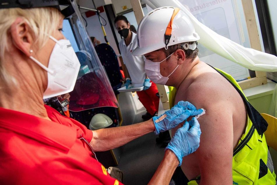Ein Seefahrer wird in einem Bus des Deutschen Roten Kreuzes am Hafen geimpft.