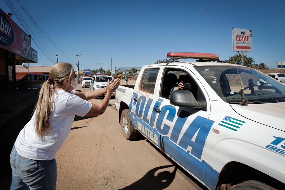 Anwohner klatschen, als die Polizei nach einem Großeinsatz gegen den Schwerverbrecher Lázaro Barbosa (†32) durch die Stadt fährt.
