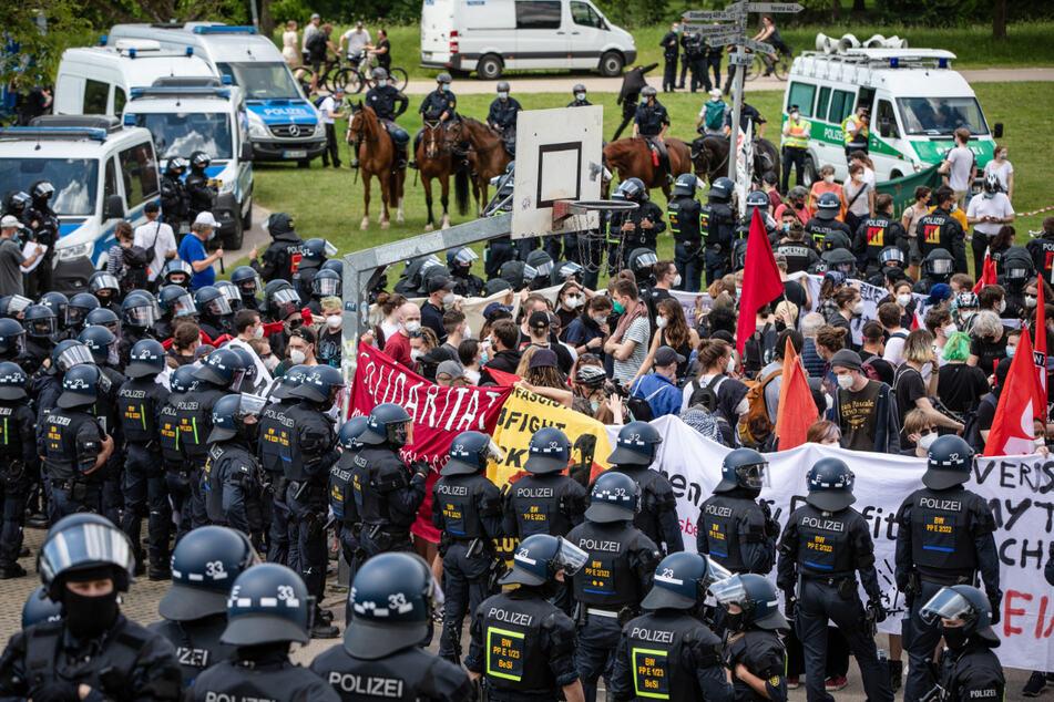 Linke Gegendemonstranten und Polizei stehen sich gegenüber.