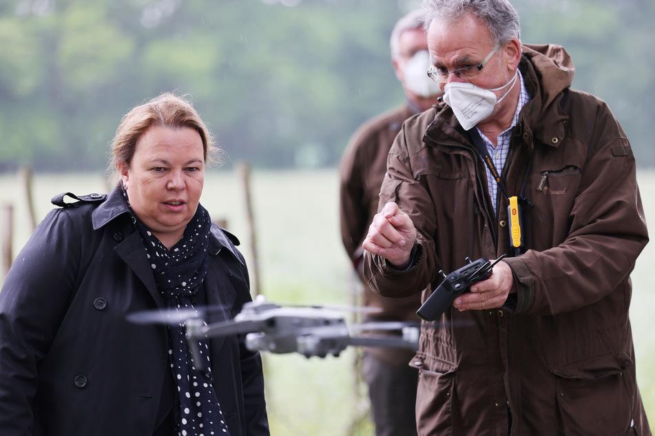 NRW-Umweltministerin Ursula Heinen-Esser (l., 55) schaut sich die Bedienung einer Drohne mit Wärmebildkamera durch einen Jäger an.