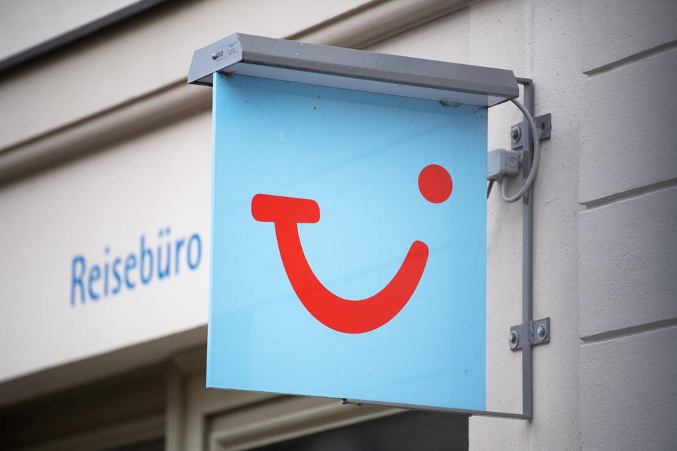 Das Logo des Reiseunternehmens TUI hängt neben einem geschlossenen Reisebüro in der Innenstadt.