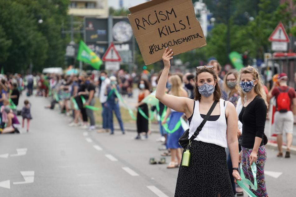 """Eine Teilnehmerin der Demonstration des Bündnisses """"Unteilbar"""" gegen soziale Ungerechtigkeiten und Rassismus trägt ein Plakat mit der Aufschrift """"Racism Kills! #Blacklivesmatter""""."""