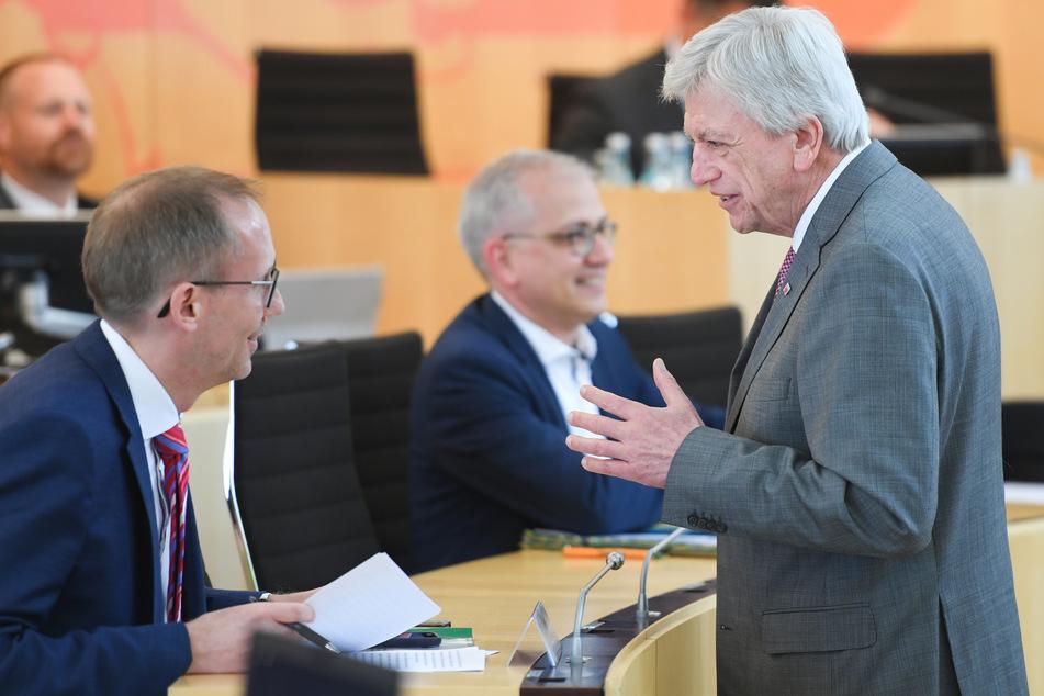 Kai Klose (Bündnis 90/Die Grünen, l), Sozialminister des Landes Hessen, und Volker Bouffier (CDU, r), Ministerpräsident des Landes Hessen, unterhalten sich zu Beginn der Plenarsitzung des hessischen Landtags im Beisein von Tarek Al-Wazir (Bündnis 90/Die Grünen), miteinander.