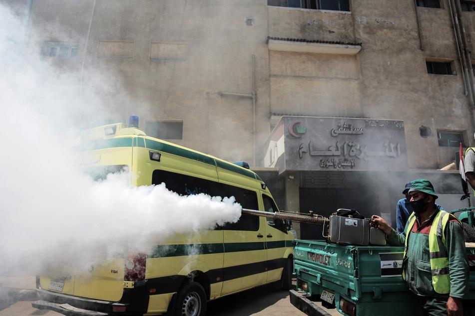 Arbeiter desinfizieren vor dem Al-Munira General Hospital in der Innenstadt von Kairo als Vorsichtsmaßnahme einen Rettungswagen.