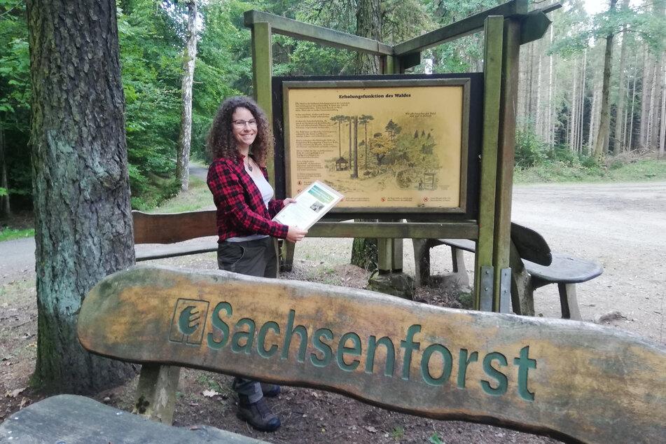 """Sarah-Louise Hetzel im Werdauer Wald vor einer Lehrtafel, die sie """"modernisieren"""" möchte."""