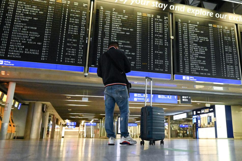 Ein Mann steht in Terminal 1 des Frankfurter Flughafens in der Abflughalle vor einer großen Anzeigentafel.