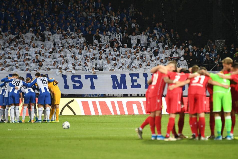 Die Spieler von Hertha (l) und Unions schwören sich vor dem Anpfiff auf das Derby ein.