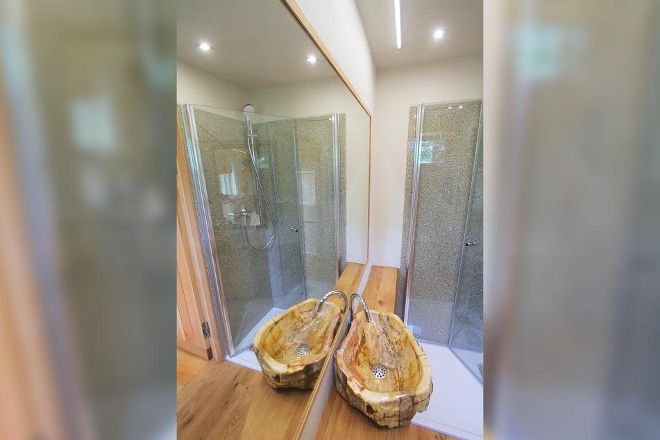 Große Dusche mit Glaswand, dazu ein Waschbecken aus versteinertem Holz - ein edles Tiny-House.