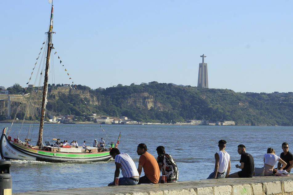 Menschen sitzen an der Küste in Cais do Sodre in Portugal. Wegen der starken Verbreitung der Delta-Variante des Coronavirus schränkt die Bundesregierung die Einreise aus Portugal und Russland massiv ein.