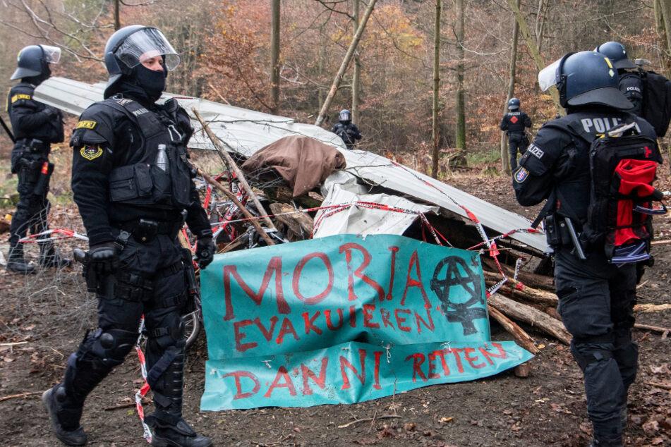 Polizisten stehen am zweiten Tag des Großeinsatzes während der Räumung von Barrikaden im Dannenröder Wald neben einem Banner.
