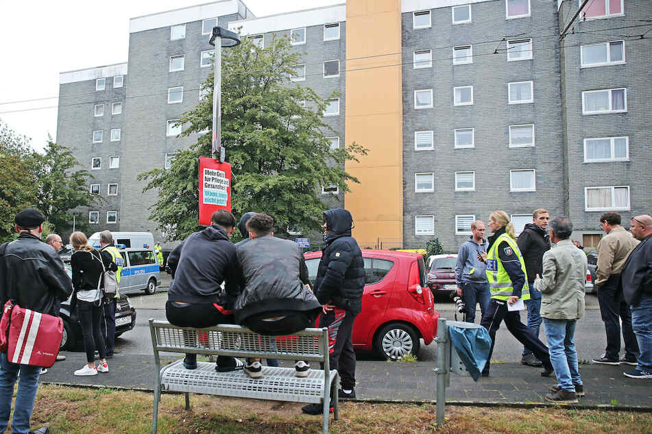 Schaulustige, Reporter und Anwohner stehen vor dem Mehrfamilienhaus in Solingen.