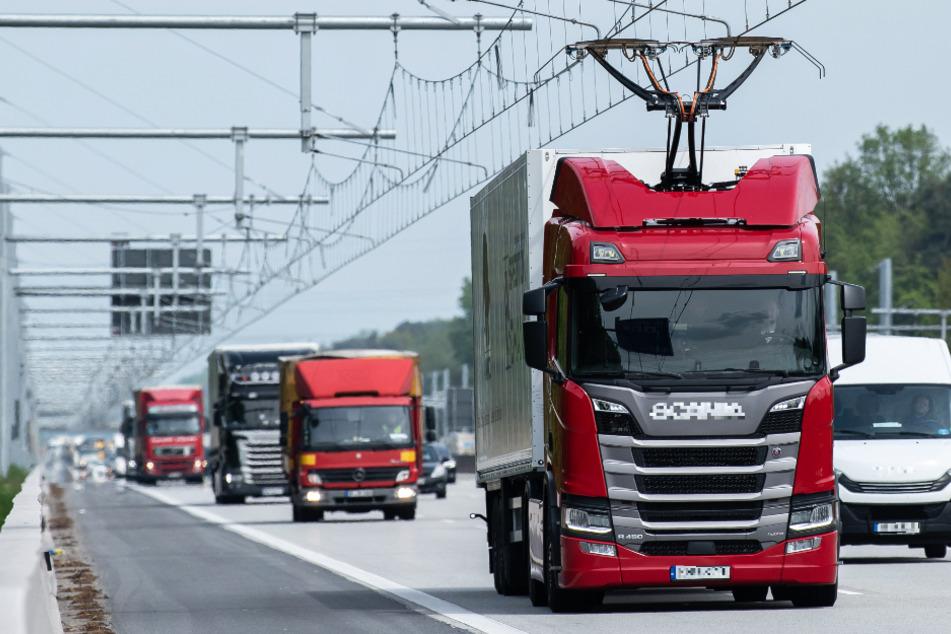 Ein Lastwagen fährt mit ausgefahrenem Stromabnehmer auf der Teststrecke für E-Lastwagen mit Oberleitung auf der A5.