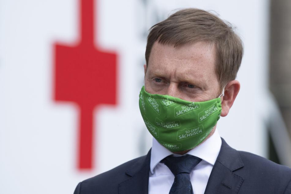 Michael Kretschmer (CDU), Ministerpräsident von Sachsen, steht während einer Übergabe von 10.000 FFP2-Schutzmasken mit einer Mund-Nasen-Bedeckung vor der Staatskanzlei.