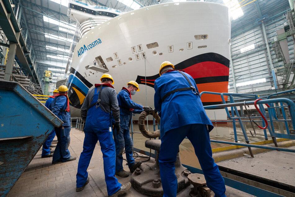 """Arbeiter stehen vor dem Bug der """"Aida Cosma"""". Das Kreuzfahrtschiff ist 337 Meter lang."""