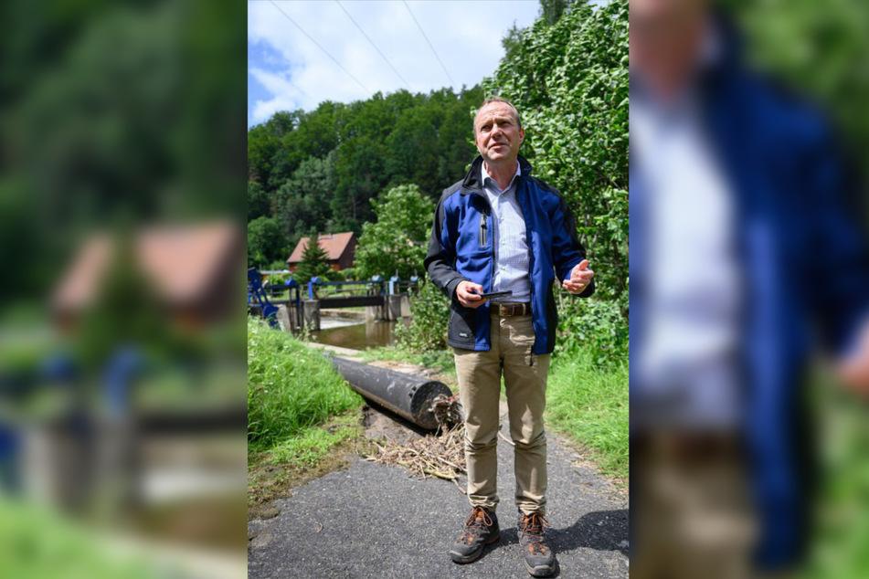 Vor dem Wehr in Porschdorf versuchte sich Umweltminister Wolfram Günther (Grüne) am Montag an einer ersten Schadensbilanz.