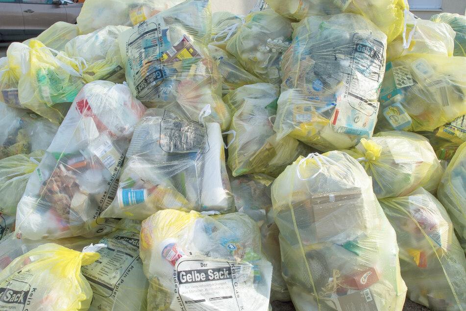 Gelbe Säcken, gefüllt mit Verpackungsabfall, liegen zur Abholung bereit. (Archivbild)