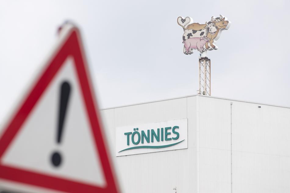 """Blick auf ein Geschäftslogo von Tönnies auf einer Produktionshalle hinter einem Verkehrsschild """"Gefahrenstelle""""."""