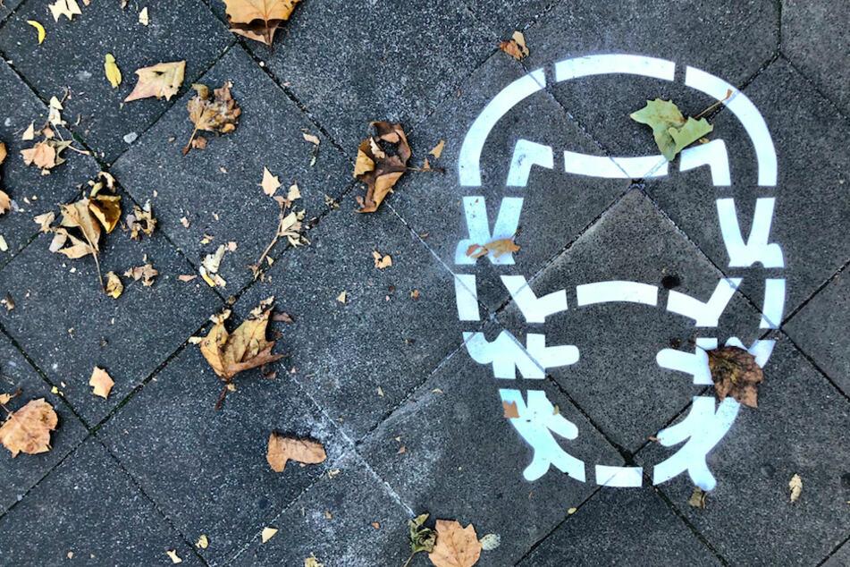 Eine Bodenmarkierung verweist auf die Maskenpflicht.