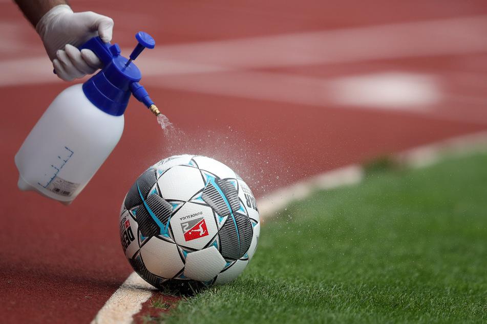 Ein Mitarbeiter desinfiziert einen Spielball.
