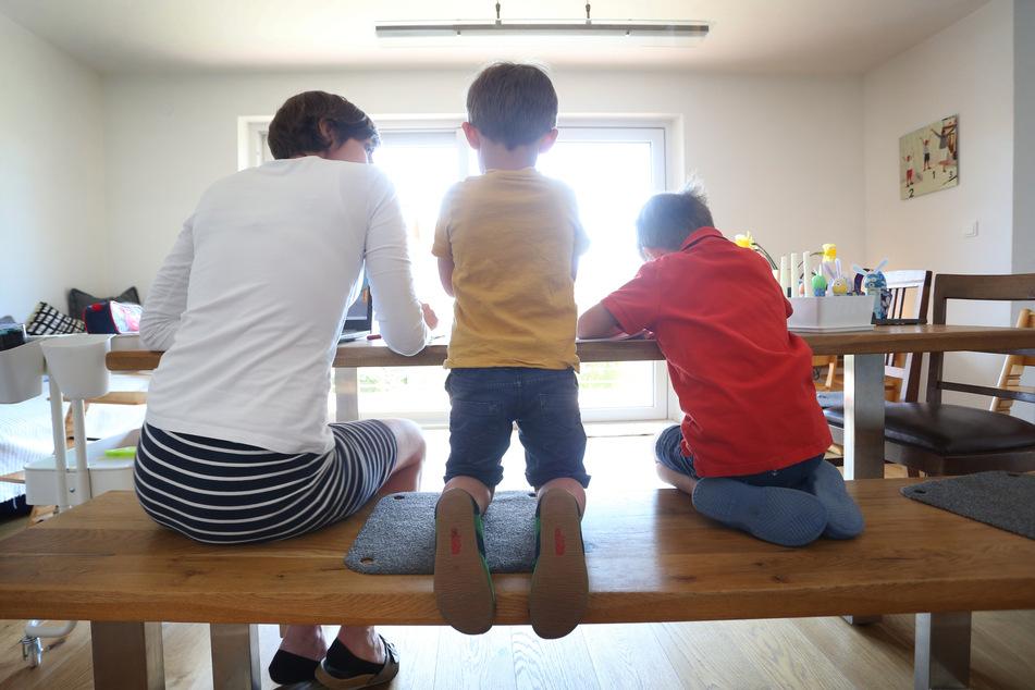 Die Mutter des sechsjährigen Jakob und des vierjährigen Valentin sitzt Zuhause neben ihren Kinder, während diese malen und ein Buch ansehen. (Symbolbild)