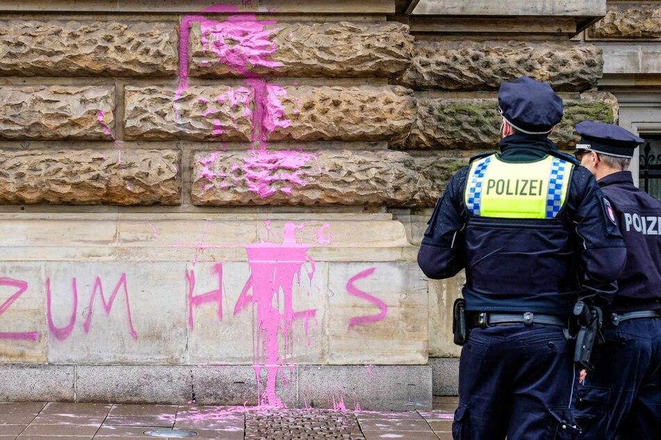 Zwei Polizisten stehen vor dem mit Farbe beschmierten Hamburger Rathaus.
