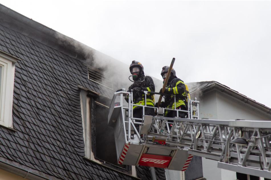 Aus dem Fenster eines Mehrfamilienhauses dringt Rauch.