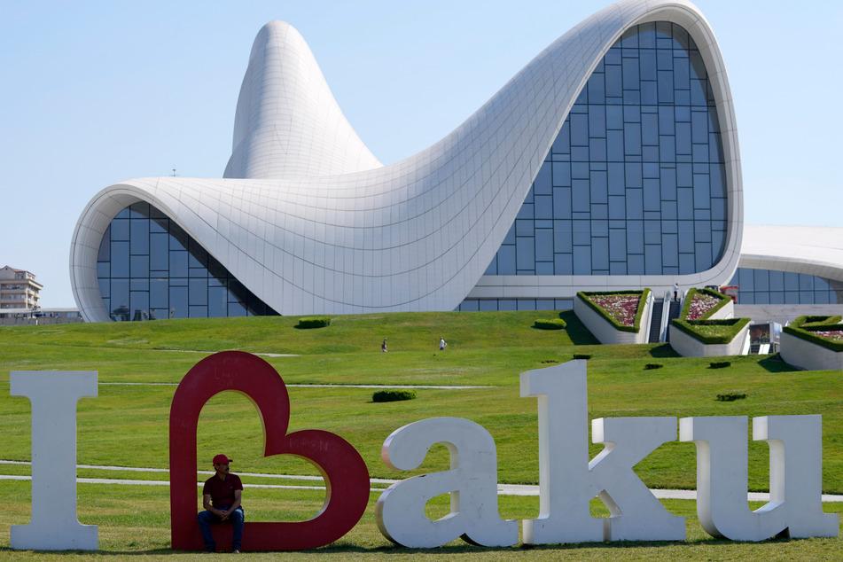 Baku: Ein Mann sitzt in einem übergroßen Herz vor dem Heydar-Aliyev-Kulturzentrum vor der bevorstehenden Fußball-Europameisterschaft.