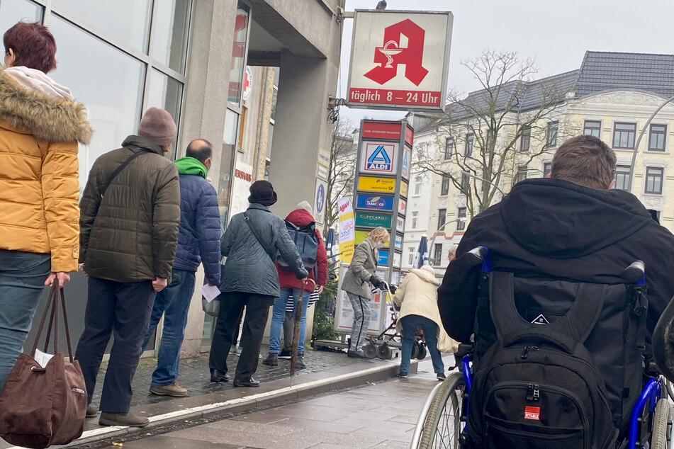Kunden warten vor einer Apotheke in Hamburg. Menschen ab 60 Jahren und Personen mit bestimmten chronischen Erkrankungen können ab Dienstag drei FFP2-Masken kostenlos in Apotheken erhalten.