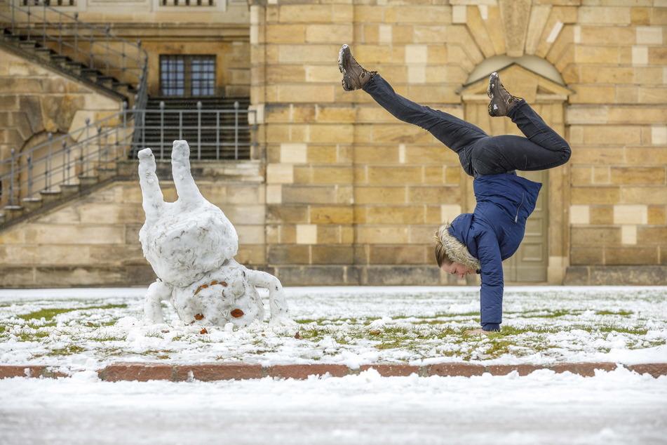 Stephanie Scheffler (33) turnt mit einem Schneemann im Großen Garten.